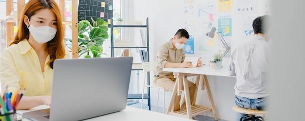 Aziatische vrouw draagt gezichtsmasker voor sociale afstand in een nieuwe normale situatie voor viruspreventie tijdens het gebruik van een laptop en gescheiden door een acryl scheidingswand op kantoor. leven en werk na het coronavirus. Gratis Foto