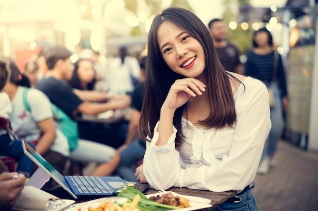 Aziatische vrouw eet straatvoedsel en ze werkt vanuit haar bedrijf Gratis Foto