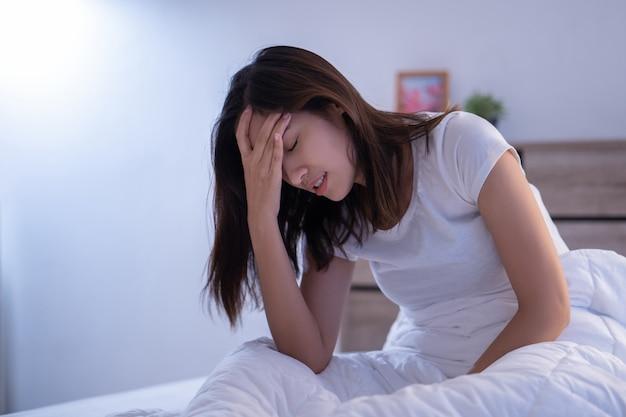 Aziatische vrouw heeft hoofdpijn in de ochtend op het bed Premium Foto