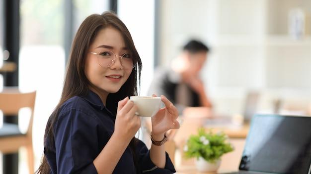 Aziatische vrouw het drinken koffie in een bureau Premium Foto