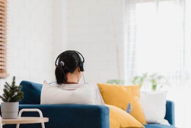 Aziatische vrouw het luisteren muziek en het gebruiken van lijst Gratis Foto