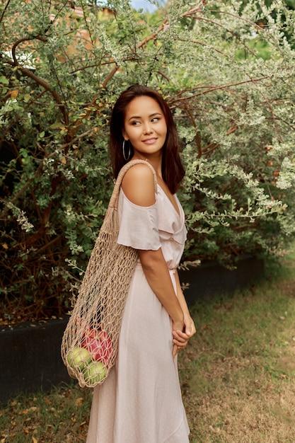 Aziatische vrouw in jurk met eco-vriendelijke mesh shopper tas met verse tropische vruchten. Gratis Foto