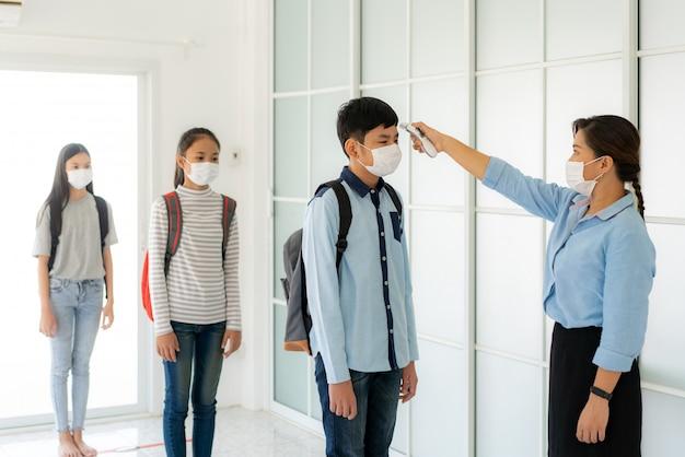 Aziatische vrouw leraar met behulp van thermometer screening student voor koorts Premium Foto