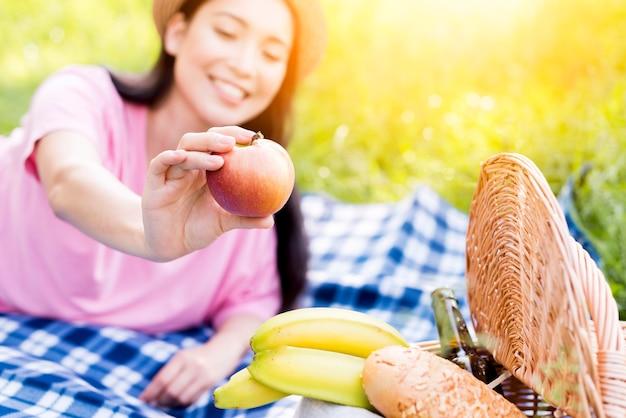 Aziatische vrouw met appel in de hand Gratis Foto