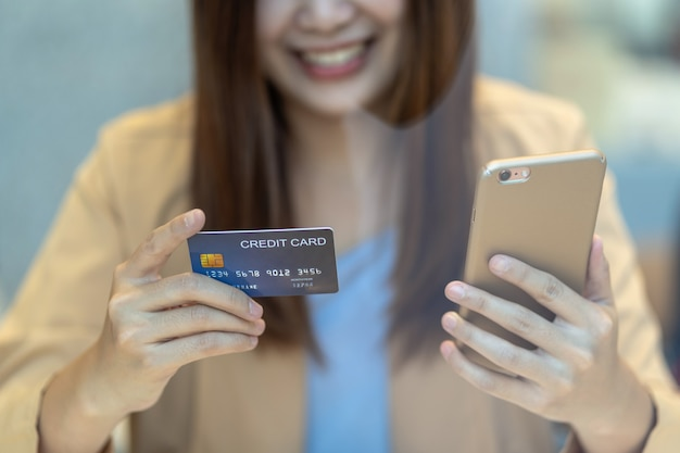 Aziatische vrouw met behulp van creditcard met mobiel voor online winkelen Premium Foto