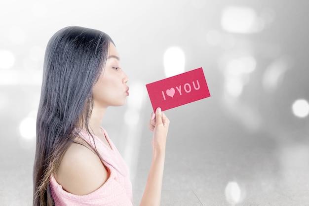 Aziatische vrouw met een rood papier met i love you-tekst met wazig lichte achtergrond. valentijnsdag Premium Foto