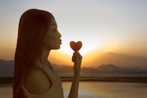 Aziatische vrouw met het rode hart met een avondrood achtergrond. valentijnsdag Premium Foto