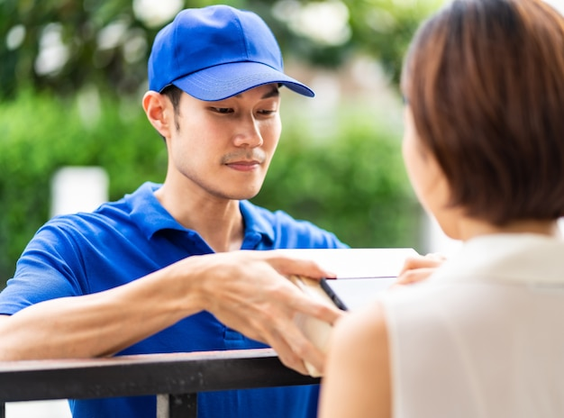 Aziatische vrouw ondertekent elektronische handtekening naar draagbaar mobiel apparaat na ontvangstpakket Premium Foto