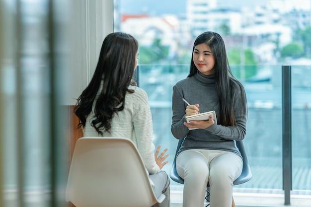 Aziatische vrouw professionele psycholoog arts die het consult geeft aan vrouwelijke patiënten Premium Foto