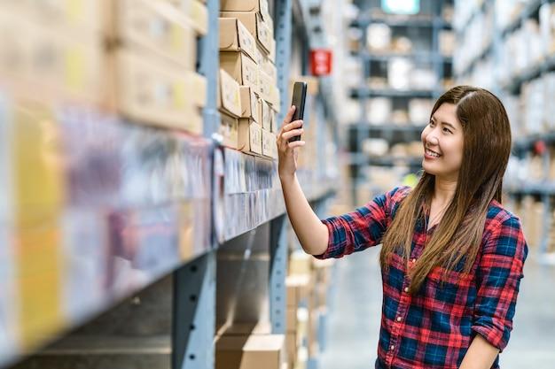 Aziatische vrouw scannen van de qr-code via de mobiele telefoon voor het controleren van goederenvoorraad en prijs in magazijn Premium Foto