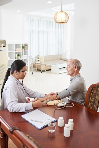 Aziatische vrouwelijke arts die de bloeddruk van de patiënt meet tijdens huisbezoek Gratis Foto