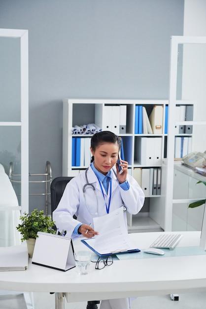 Aziatische vrouwelijke arts die op mobiele telefoon in bureau spreekt en verslagen bekijkt Gratis Foto