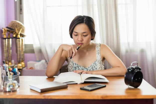 Aziatische vrouwelijke student gelezen boek voor eindexamen Premium Foto