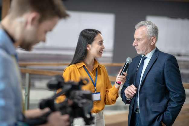 Aziatische vrouwelijke verslaggever met een microfoon in haar hand tijdens het gesprek met een zakenman Premium Foto