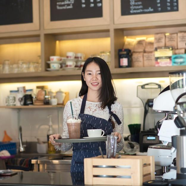 Aziatische vrouwen barista die en koffiemachine in de teller van de koffiewinkel glimlachen met behulp van Premium Foto