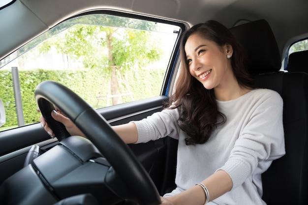 Aziatische vrouwen besturen van een auto en glimlachen gelukkig met blije positieve uitdrukking tijdens de rit om te reizen Premium Foto