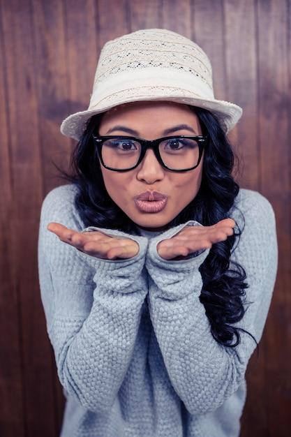 Aziatische vrouwen blazende kus aan de camera tegen houten muur Premium Foto