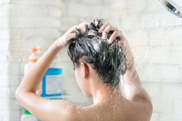 Aziatische vrouwen die baden en ze was aan het baden en haar wassen. ze is gelukkig Premium Foto