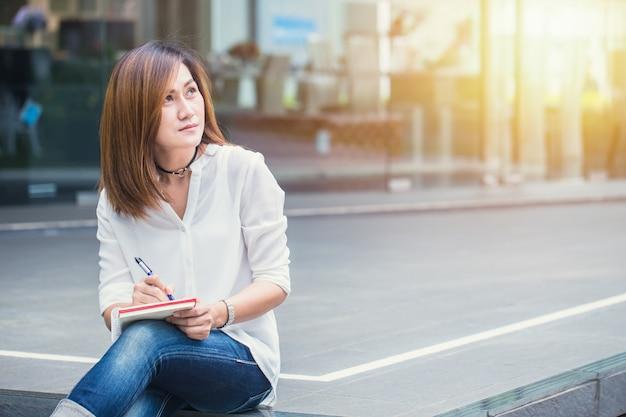 Aziatische vrouwen die bij openluchthand met pen het schrijven nota windende bedrijfsprojectactie woking Premium Foto