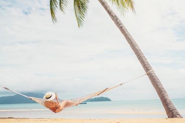 Aziatische vrouwen die in de vakantie van de hangmatzomer ontspannen op strand Premium Foto
