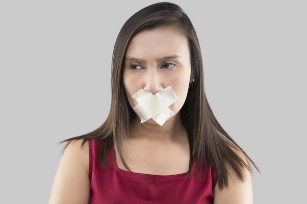 Aziatische vrouwen in rode jurken gebruiken afplakband om de mond te sluiten omdat ze geen commentaar willen geven op grijs Premium Foto