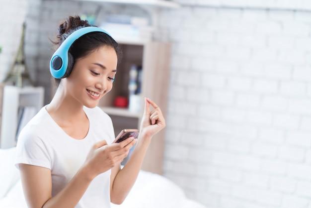 Aziatische vrouwen luisteren naar muziek en ze zingt vrolijk in de kamer Premium Foto