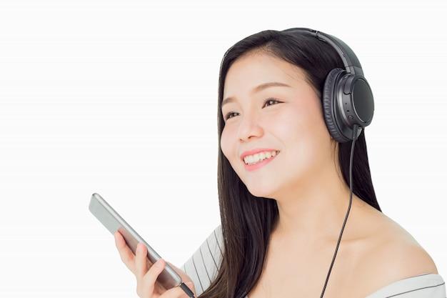 Aziatische vrouwen luisteren naar muziek van zwarte hoofdtelefoons. in een comfortabele en goede stemming. Premium Foto