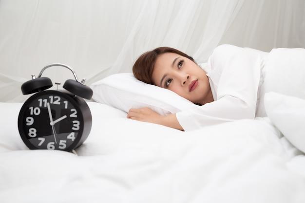 Aziatische vrouwen met gevoelens van hulpeloosheid en hopeloosheid op wit bed in de slaapkamer, ofwel slapeloosheid, depressie symptomen en waarschuwingssignalen concept Premium Foto