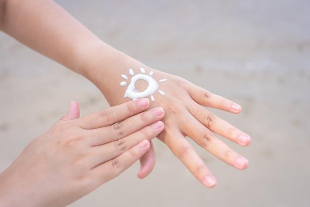 Aziatische vrouwen passen zonnebrandcrème op de handen en armen toe. om de huid tegen zonlicht te beschermen, Premium Foto