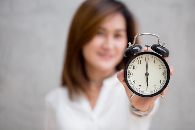Aziatische vrouwen tonen kloktijden om 6 uur, het is tijd om iets concept te doen Premium Foto
