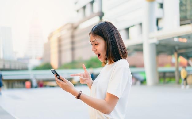 Aziatische vrouwen van gelukkig glimlachend en slimme telefoon met verbaasd houden voor succes. Premium Foto