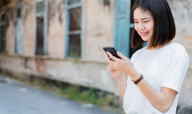 Aziatische vrouwen van gelukkig lachend en met behulp van smartphone. Premium Foto