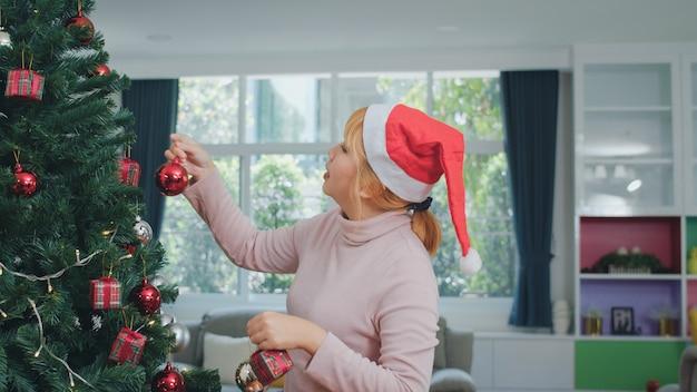 Aziatische vrouwen versieren kerstboom op kerstfestival. het vrouwelijke tiener gelukkige glimlachen viert thuis de vakantie van de kerstmiswinter in woonkamer. Gratis Foto