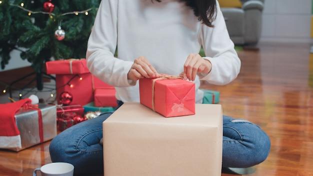 Aziatische vrouwen vieren kerstfestival. de vrouwelijke sweater van de tienerslijtage en de kerstmishoed ontspannen gelukkige verpakkende giften dichtbij kerstboom genieten samen thuis van de vakantie van de kerstmiswinter in woonkamer. Gratis Foto
