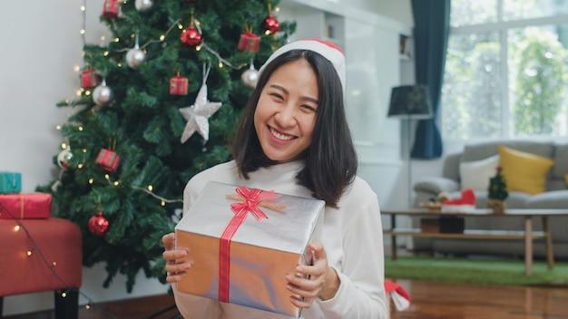 Aziatische vrouwen vieren kerstfestival. de vrouwelijke sweater van de tienerslijtage en kerstmishoed ontspant gelukkige greepgift glimlachend dichtbij kerstboom geniet thuis van de vakantie van de kerstmiswinter in woonkamer. Gratis Foto