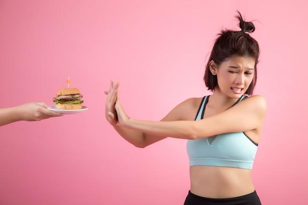 Aziatische vrouwen weigeren fastfood vanwege afvallen op roze Gratis Foto