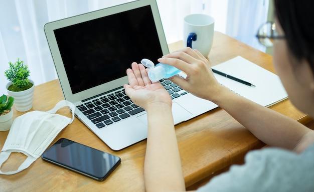 Aziatische vrouwen werken thuis met een notebook, gebruiken alcoholgel uit de fles om de handen schoon te maken en verspreiding van het coronavirus tijdens de crisis van covid-19 te voorkomen. Premium Foto