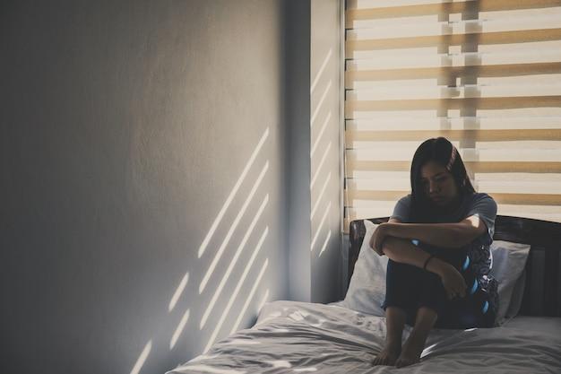 Aziatische vrouwen zitten knuffelen hun knieën in bed Premium Foto