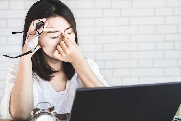 Aziatische vrouwenarbeider die aan oogspanning lijden Premium Foto