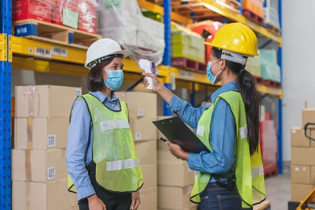 Aziatische vrouwenarbeider draagt gezichtsmasker in veiligheidsvest met behulp van thermometer infraroodscan om de lichaamstemperatuur te controleren met collega voordat ze in magazijnfabriek werken tijdens coronavirus pandemie Premium Foto