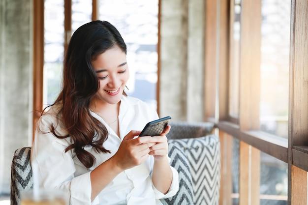 Aziatische vrouwenglimlach met het mobiele telefoon ontspannen in koffie Premium Foto
