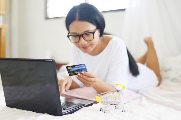 Aziatische vrouwenhanden die creditcard houden en laptop voor online het winkelen met boodschappenwagentje op het bed met behulp van. Premium Foto