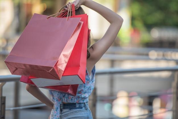 Aziatische vrouwenholding het winkelen zakken en opgeheven handen omhoog Premium Foto