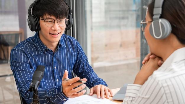 Aziatische vrouwenradiopresentatoren gebaren naar microfoon tijdens het interviewen van een mannelijke gast in een studio terwijl ze samen een podcast opnemen voor een online show in de studio. Premium Foto