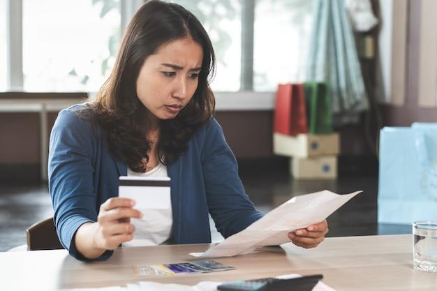 Aziatische vrouwenspanning met creditcardschuld. Premium Foto