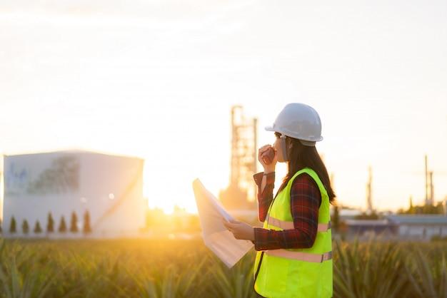 Aziatische vrouwentechnicus industriële ingenieur die walkie-talkie gebruiken en blauwdruk houden werkend in olieraffinaderij voor bouwterrein Premium Foto