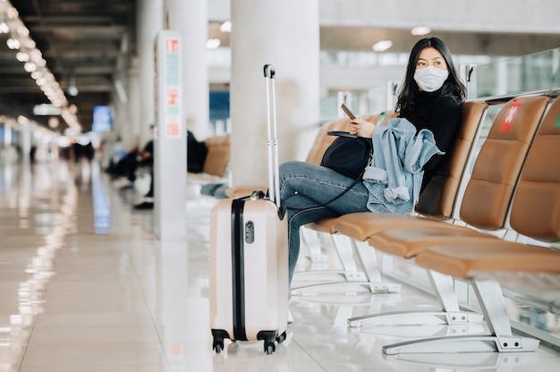 Aziatische vrouwentoerist die gezichtsmasker draagt dat op sociale afstandsstoel zit Premium Foto