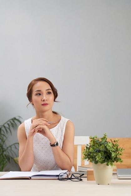 Aziatische vrouwenzitting bij bureau met dagboek, weg kijkend en denkend Gratis Foto