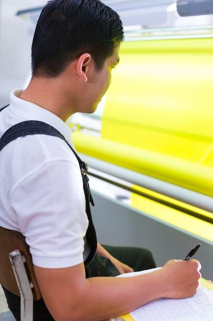 Aziatische werknemer controleert stoffen in textielfabriek Premium Foto