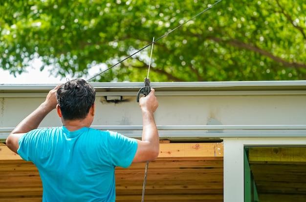Aziatische werknemer last de stalen stok om een constructie te creëren voor de waterafvoer op het dak Premium Foto